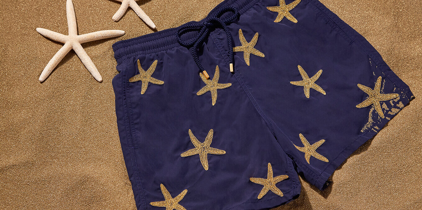 Blue men's swimsuit embroidered with gold starfish threads