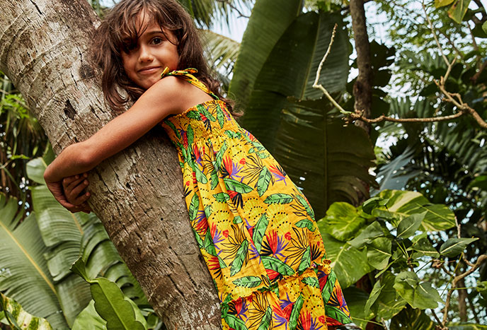 Little girl wearing a go banana dress yellow and green standing on a tree
