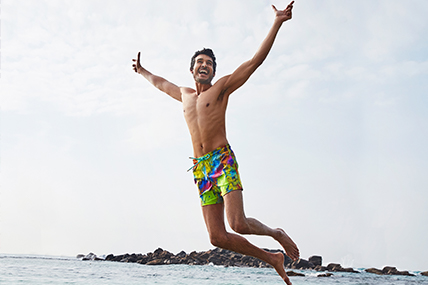 Man jumping in the sea, wearing a colorful men swimwear