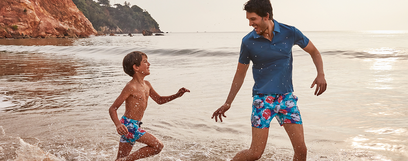A father and his son play on the beach and wear the same swimming trunks. It was created to protect Polynesian turtles.
