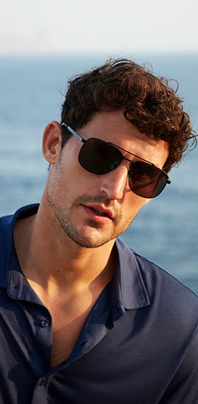 A men wearing a navy polo and a pair of black sunglasses