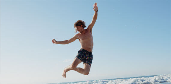 A man wearing a swimsuit jumping near the sea